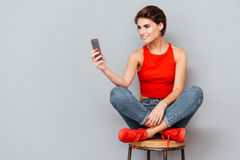 Smiling brunette woman sitting on the chair and using smartphone Royalty Free Stock Image