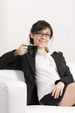 Smiling brunette woman on sofa Royalty Free Stock Photos