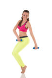 Smiling brunette woman in sports neon yellow leggings and pink bra doing complex exercises for muscles of back, legs, buttocks and Royalty Free Stock Image