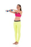 Smiling brunette woman in sports neon yellow leggings and pink bra doing complex exercises for muscles of hands using dumbbell Royalty Free Stock Image