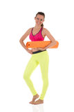 Smiling brunette woman in sports neon yellow leggings and pink bra standing with the orange rolled mat Stock Photo