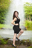 Smiling brunette woman standing at pond Stock Photo