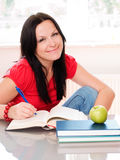 Smiling brunette woman studying Royalty Free Stock Images