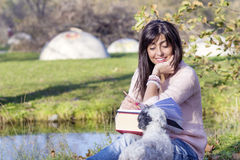 Smiling  brunette woman studying in the park  with her white  dog Stock Photos