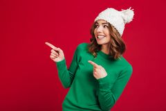 Smiling brunette woman in sweater and funny hat pointing away Royalty Free Stock Photography