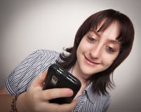 Smiling Brunette Woman Using Cell Phone Royalty Free Stock Photography