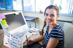 Smiling brunette working with photographs and digitizer Royalty Free Stock Photos