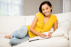 Smiling brunette writing on note pad Royalty Free Stock Images