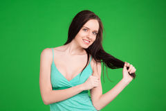 Smiling brunetter girl holding her hair over green background Royalty Free Stock Image
