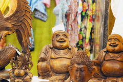 Smiling Buddah. Smiling wooden buddah statue between other wooden statues, horizontal image stock images