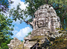 Smiling Buddha face on the arch in Angkor Wat. Smiling face sculpture on the stone tower in khmer Angkor Wat temple in Cambodia Stock Images