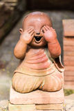 Smiling buddhist novice made of clay , Thai style Royalty Free Stock Photography