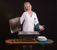 Smiling Buffet Chef. Assertive uniformed female Chef presenting buffet Stock Photos