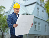 Smiling builder with blueprint over house Stock Photography