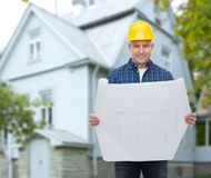 Smiling builder with blueprint over house. Repair, construction, building, people and maintenance concept - smiling male builder or manual worker in helmet with Stock Photography