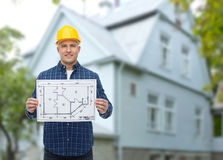 Smiling builder with blueprint over house. Repair, construction, building, people and maintenance concept - smiling male builder or manual worker in helmet with Stock Images