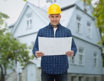 Smiling builder with blueprint over house. Repair, construction, building, people and maintenance concept - smiling male builder or manual worker in helmet with Stock Image