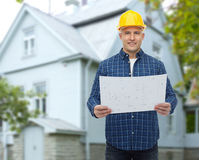 Smiling builder with blueprint over house. Repair, construction, building, people and maintenance concept - smiling male builder or manual worker in helmet with Stock Photos
