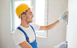 Smiling builder with grinding tool indoors Royalty Free Stock Photography