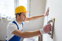 Smiling builder with grinding tool indoors Stock Image