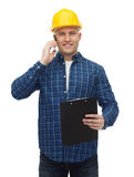 Smiling builder in helmet calling on smartphone Stock Images