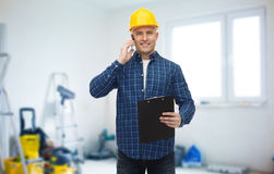 Smiling builder in helmet calling on smartphone Royalty Free Stock Photography