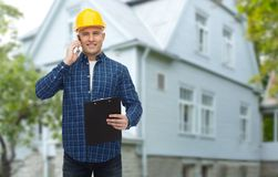 Smiling builder in helmet calling on smartphone Royalty Free Stock Image