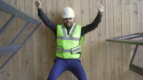 Smiling builder in the helmet and green jacket lying on the floor showing victory gestures and looking up. Profession. Concept. The guy resting after work. Top stock footage