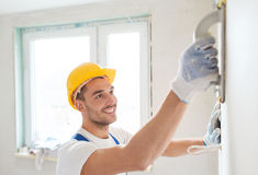 Smiling builder working with grinding tool indoors Stock Photos