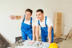 Smiling builders with blueprint Stock Image