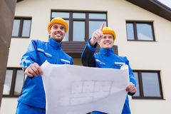 Smiling builders with blueprint pointing finger Royalty Free Stock Photos