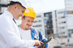 Smiling builders in hardhats with tablet pc Stock Images