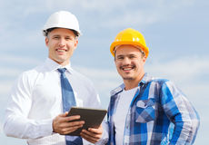 Smiling builders in hardhats with tablet pc Royalty Free Stock Photo