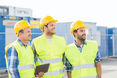 Smiling builders in hardhats with tablet pc. Business, building, teamwork, technology and people concept - group of smiling builders in hardhats with tablet pc Royalty Free Stock Images