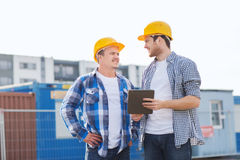 Smiling builders in hardhats with tablet pc Royalty Free Stock Photos