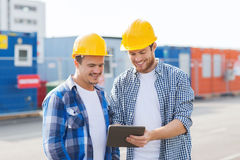 Smiling builders in hardhats with tablet pc Royalty Free Stock Image