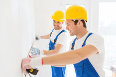 Smiling builders with measuring tape indoors Stock Image