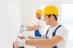 Smiling builders with measuring tape indoors. Building, teamwork, measurement and people concept - group of smiling builders in hardhats with measuring tape royalty free stock photography
