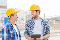 Smiling builders with tablet pc outdoors Royalty Free Stock Image