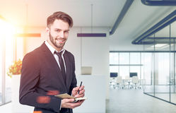Smiling buisnessman in an office lobby Royalty Free Stock Images