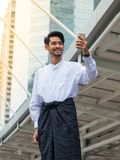 Burmese businessman using phone. Smiling Burmese businessman wearing traditional Burmese business attire looks at a smartphone screen while standing inside a royalty free stock photos