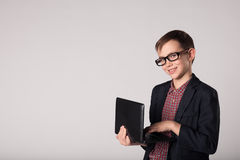 Smiling business child holding laptop in his hands. Young smiling business child in a suit and eyeglasses holding laptop in his hands Stock Photos