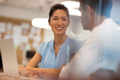 Smiling business colleagues discussing while working in office Stock Image