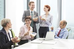Smiling business colleagues eating lunch in boardroom during meeting at office stock photos