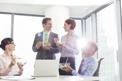 Smiling business colleagues eating lunch in boardroom during meeting at office royalty free stock photography