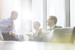 Smiling business colleagues eating lunch while sitting in boardroom during meeting at office royalty free stock image