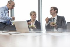 Smiling business colleagues eating lunch while sitting in boardroom during meeting at office royalty free stock photo