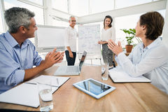 Smiling business colleagues ending presentation Stock Photo
