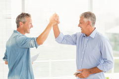 Smiling business colleagues giving high-five. At the office Stock Image