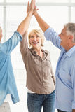 Smiling business colleagues giving high-five. Three smiling business colleagues giving high-five at the office Royalty Free Stock Image